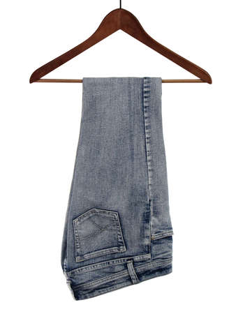 Blue jeans on a wooden hanger, isolated on white background.