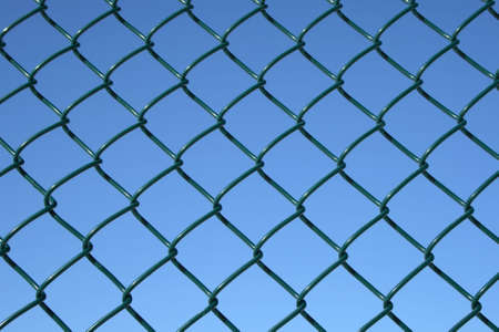 Green chain link fence on a blue sky background. photo