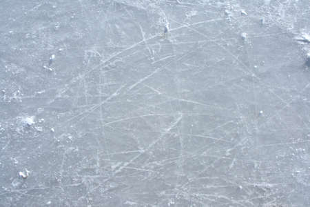 Surface of an outdoor ice rink replete with skate marks.