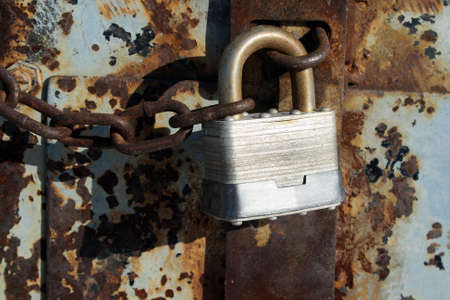 Iron lock and chain on an old rusty door. Stock Photo - 768789