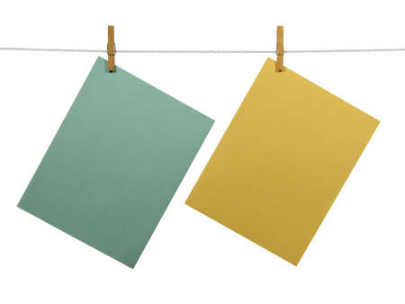 clothespins: Green and yellow blank paper sheets on a clothes line, isolated on white background. With clipping path. Stock Photo