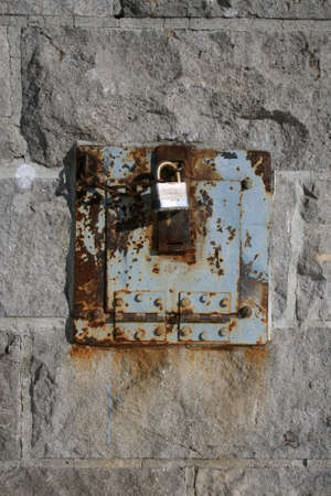 Iron lock and rusty metal on a stone wall. photo