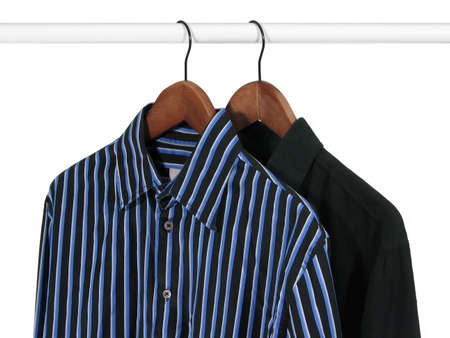 Black and blue shirts on hangers on a rack, on white background. photo