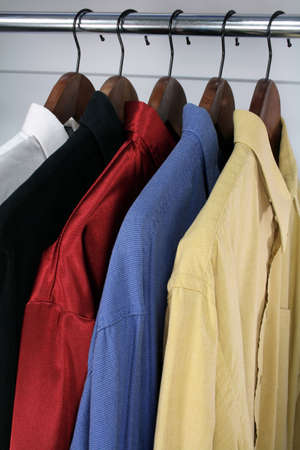 hangers: Shirts of different colors on wooden hangers. Stock Photo