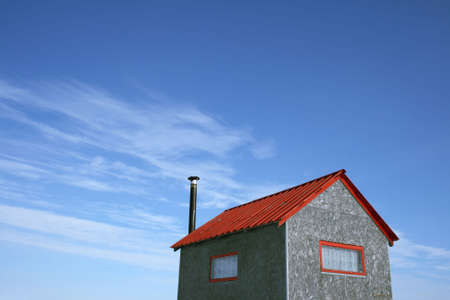 shanty: Little house with red roof and chimney and spacious blue sky (ice fishing hut). Stock Photo