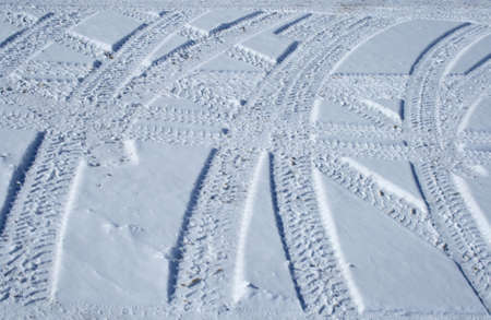 Vehicle tracks crossing the snowy winter terrain in different directions. photo