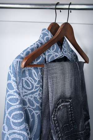 closet: Blue jeans and shirts on wooden hangers in a closet.