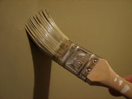 Home improvement: paint brush painting a wall. Stok Fotoğraf