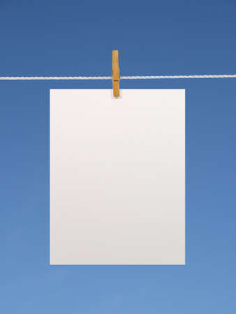 Blank paper sheet on a clothes line against the blue sky. Contains two clipping paths: 1) paper, clothes line and clothespin; 2) paper only photo
