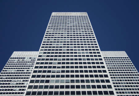 Three-part symmetrical white office building against the blue sky. photo