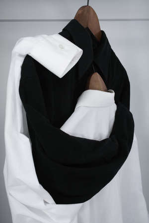 Drama in a closet. Black shirt tenderly embracing the white shirt, which hides her �head� on his chest. photo