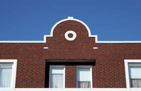Facade and ornamental rooftop of a red brick house. photo