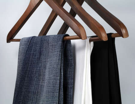 hangers: Business or casual? Blue jeans and trousers on wooden hangers.