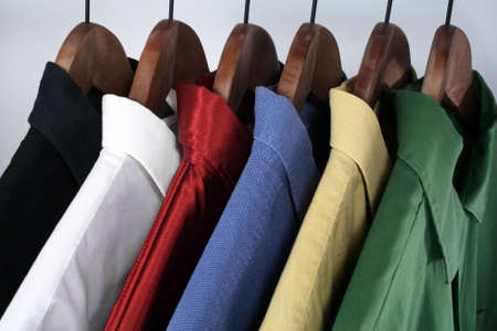 shirts on hangers: Mans wear: choice of colorful shirts on wooden hangers.