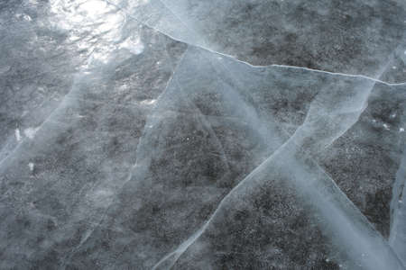 Cracked ice. Surface of a frozen river reflects the sun. Stock Photo