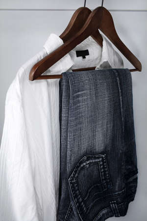 Man's clothing: blue jeans and white shirt on wooden hangers. Stock Photo - 857550
