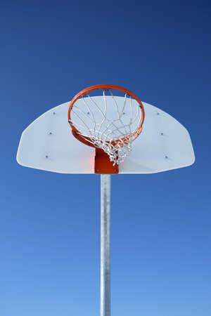 backboard: Basketball backboard, hoop and net against the blue sky.