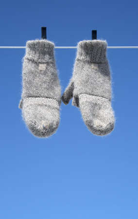 Mittens on the clothes-line hanging to dry – the winter is over Stock Photo - 867740