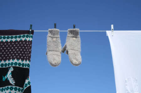 Spring laundry - mittens, sweater and t-shirt hanging to dry on a clothes-line. 版權商用圖片
