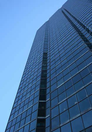 Perspective view of a blue glass-windowed skyscraper. photo