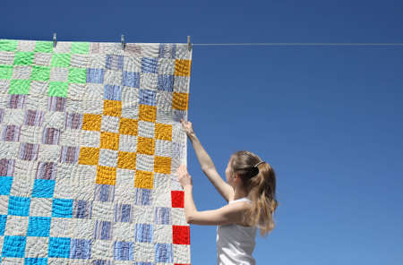 Girl touching a bright patchwork counterpane hanging to dry on a clothes-line.