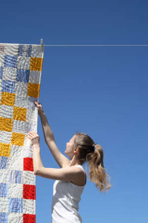 coverlet: Young woman touching a bright patchwork counterpane hanging to dry on a clothes-line. Stock Photo