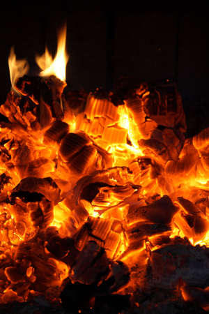 Glowing coals and fire flames in the fireplace. Stock Photo