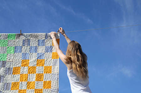 Longhaired young woman putting a bright counterpane on a clothes-line to dry in a breeze.