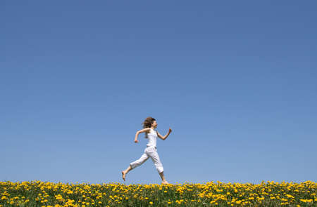 flowering field: Happy girl in summer white clothes running in a flowering dandelion field. Stock Photo
