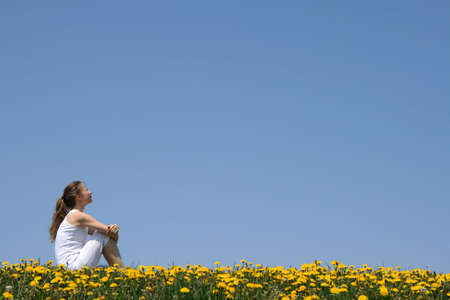 Girl in white clothes sitting in a flowering dandelion field. Stock Photo - 960288