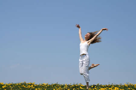 Smiling girl in summer white clothes dancing in a flowering dandelion field. Stock Photo - 963884