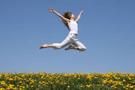 salto largo: Chica en el verano de blanco volando en un salto largo de la floraci�n de diente de le�n.