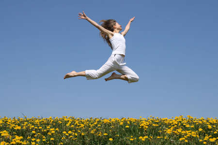 Girl in summer white clothes flying in a jump over flowering dandelion field.