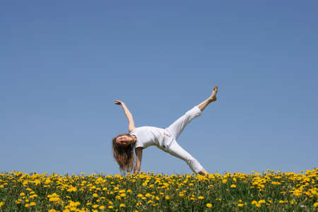 Smiling young woman in summer white clothes exercising in flowering dandelion field. Stock Photo - 963885
