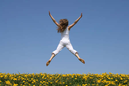Girl in summer white clothes flying in a funny jump over flowering dandelion field. photo
