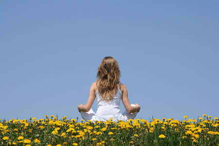 Peace of mind. Longhaired young woman in white clothes relaxing in a flowering dandelion field. photo