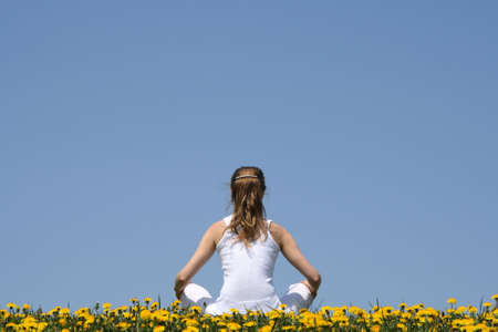 In harmony with nature. Young woman in white clothes sitting in a flowering dandelion field. photo