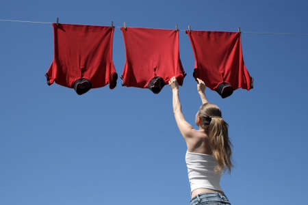 Young woman reaching red corporate t-shirts which hang to dry in a summer breeze on a clothes-line. Stock Photo - 963887