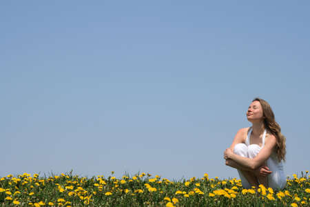 Young woman enjoying sunshine in a flowering spring field. 版權商用圖片