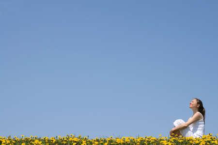 fresh air: Donna giovane graziosa che gode sole ed aria fresca in un campo flowering.