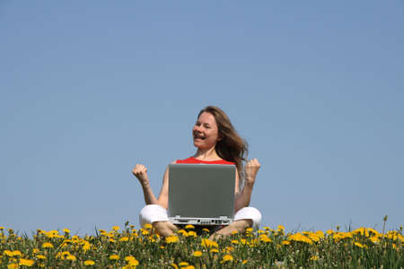 distant work: Happy successful woman with laptop in a flowering spring field.