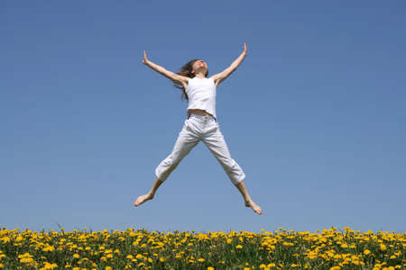 Smiling girl in summer white clothes jumping in flowering meadow.