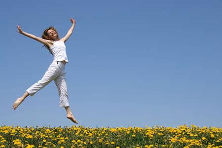 salto largo: Sonriendo muy ni�a en el verano de blanco bailando en una pradera en flor.