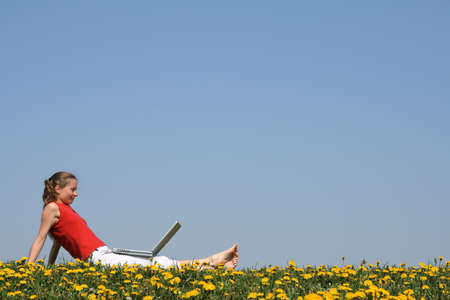 distant work: Casual young woman relaxing with laptop outdoors, in a flowering dandelion field. Stock Photo