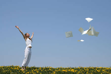 throw: Laughing girl throws in air blank paper sheets (with copy space), freeing herself from paperwork. Stock Photo