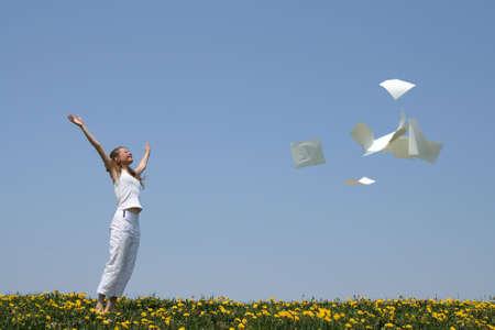 Laughing ragazza getta in aria i fogli di carta in bianco (con copia di spazio), la liberazione da se stessa carta.