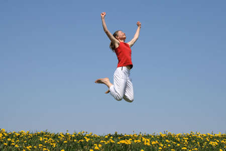 I am the winner! Smiling young woman jumps with her arms raised in joy. Stock fotó