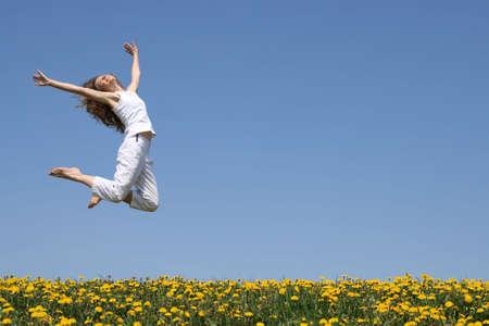 행복 한 점프에 아름 다운 미소 젊은 여자.