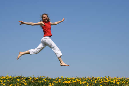 Girl in red t-shirt flying in a jump over flowering dandelion field.