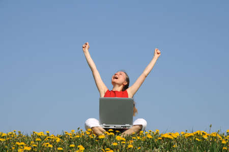 distant work: Happy young woman with laptop in a flowering spring field. Stock Photo